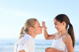 Girl apply sunscreen mum fun