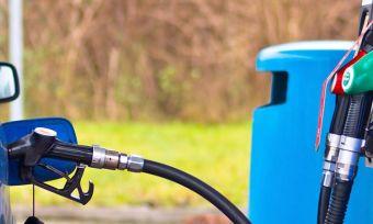 Filling up a blue car at a petrol station.