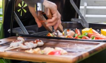 Man grilling food on barbeque with tongs
