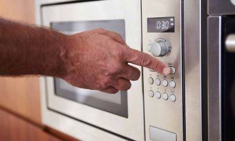 Close-up of hand using microwave