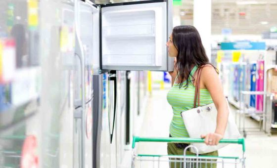 woman buys a fridge in the store