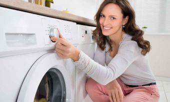 Woman Pressing Button Of Washing Machine