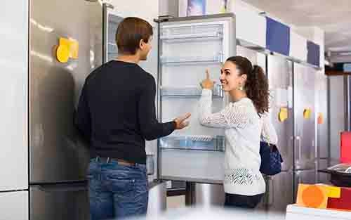 family couple choosing new refrigerator