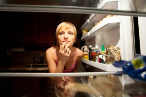 Woman thinking about her food choice inside refregirator