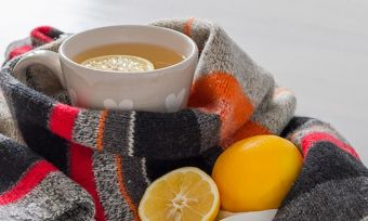 Warm tea, wrapped in a winter scarf, with lemons.