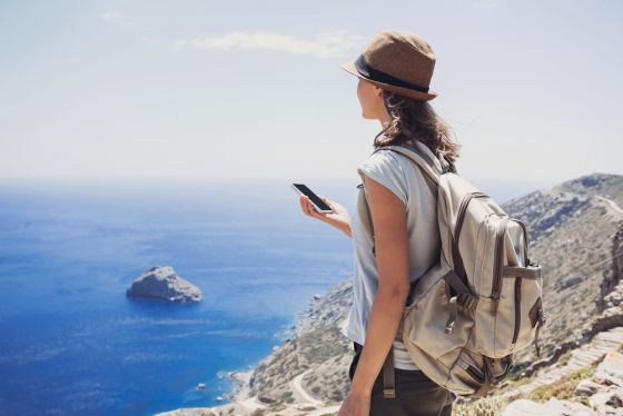 Hiking woman using smart phone, travel and active lifestyle concept