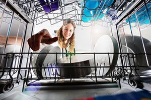 A girl reaching into a dishwasher to remove plates.