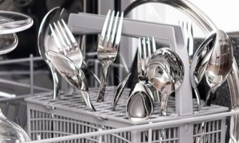 Dishwasher drawer open with cutlery and plates