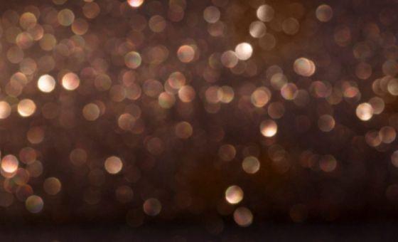Golden sparkles on a dark background.