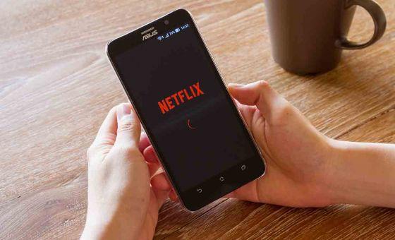 man hand holding screen shot of Netflix application
