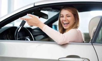 Cheerful woman sitting in a car holding new car keys.