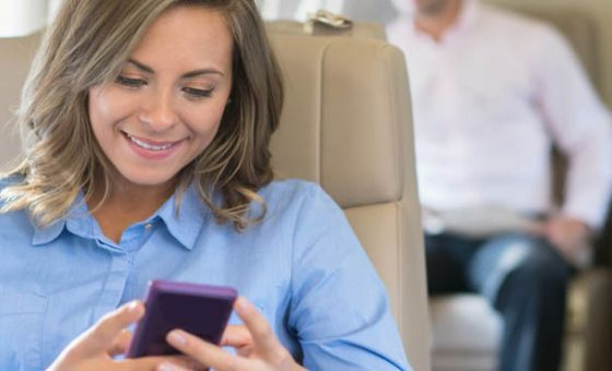 Business woman texting on plane