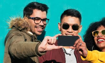 Group of friends taking group selfie with smartphone