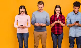 Four people holding and looking at mobile phones against yellow background