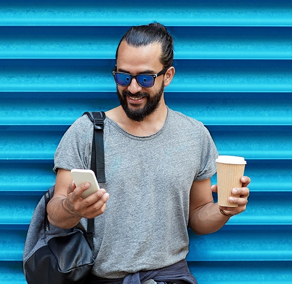 Man Holding Smartphone On Telstra Phone Plan