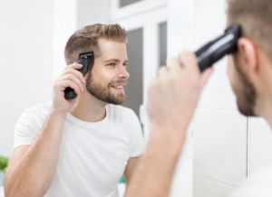 Handsome bearded man cutting his own hair with a clipper - Image