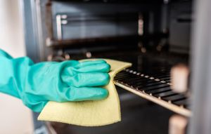 mans hand cleaning oven