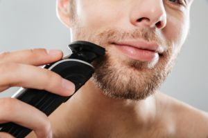 man smiling while shaving his face
