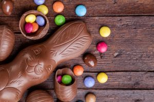 Delicious chocolate easter eggs and sweets on wood