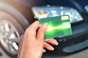 Woman hand holding green credit card using to buy a new car