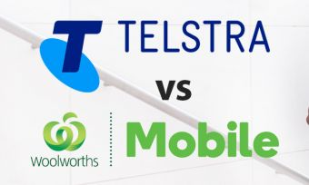 Young man talking on phone carrying books walking up stairs with Telstra and Woolworths Mobile logos