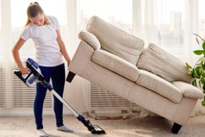 woman in white shirt and jeans cleaning carpet