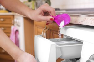 Woman throws laundry detergent into the washing