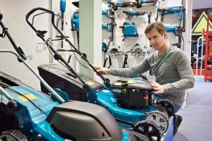 Man chooses a lawn mower in store - Image