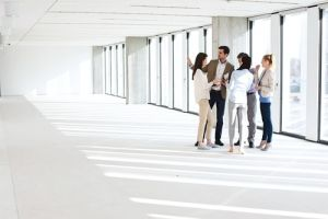 Full length of business people having discussion in empty office space - Image
