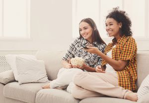 Two young women watching TV together
