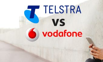 Woman holding phone with Telstra and Vodafone logos