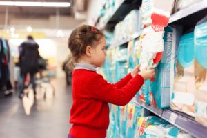 Little girl selects diapers in supermarket