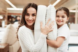mother hugs pillows in store of orthopedic mattresses