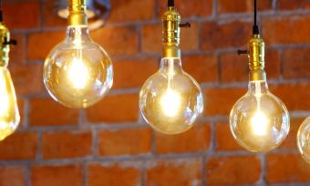 Light bulbs hanging from ceiling next to brick wall