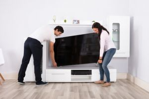 Young Couple Carrying Flat Television Screen
