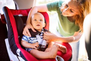 Young mother putting baby boy in the car seat