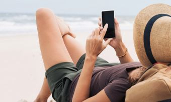 Young woman lying on beach sing mobile phone