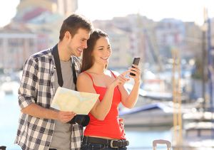 Young couple on holiday using phone and map