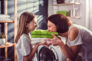 Mother and daughter smelling fresh green towels