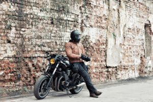 Man a motorcyclist standing with helmet