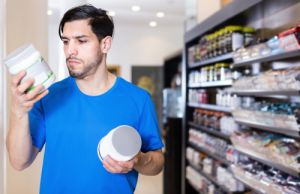 young athletic man looking sport supplements