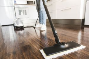 Woman washes the floor with a steam mop