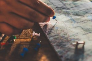 Close up hands putting pins to destination
