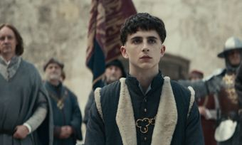 Still from Netflix movie The King showing King Henry 5 surrounded by his court