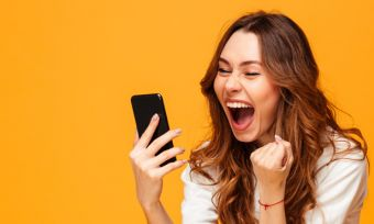 Young excited woman holding phone against orange background