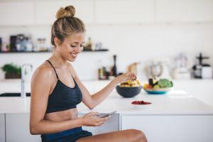woman in kitchen eating on phone
