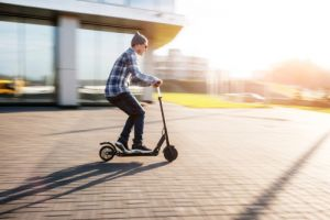 Young man in casual wear on electric kick scooter