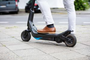 Low Section Of A Businessman Standing On Electric Scooter At Street