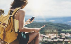 Hipster young girl with bright backpack looking at phone and map