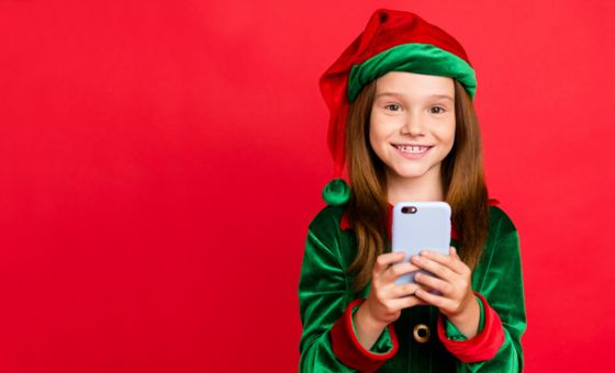 Young girl wearing elf costume holding smartphone against red background